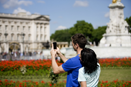 buckingham: A young couple taking a picture of Buckingham Palace