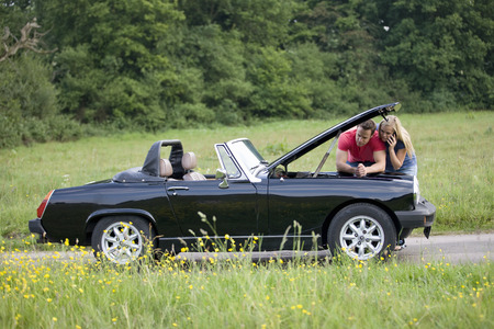 A young couple standing next to their broken down sports car speaking on a mobile phone