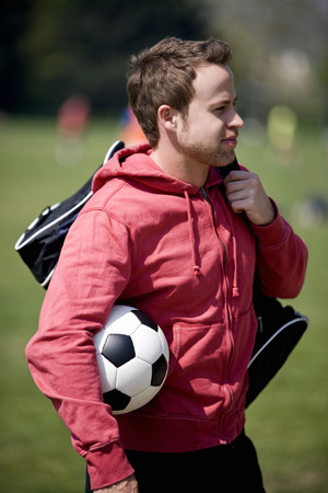 above 30: A young man standing in the park, carrying a football and a sports bag LANG_EVOIMAGES