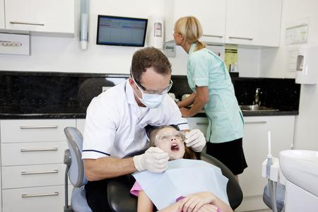 dental nurse: A male dentist examining a young girls teeth, dental nurse in the background