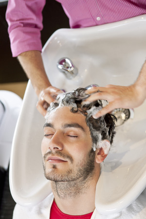 shampooing: A male hairdresser shampooing a male clients hair