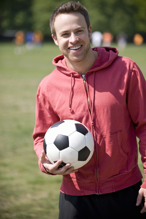 above 30: A young man standing in the park, holding a football