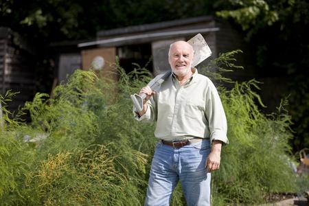 self sufficient: A senior man holding a spade on an allotment
