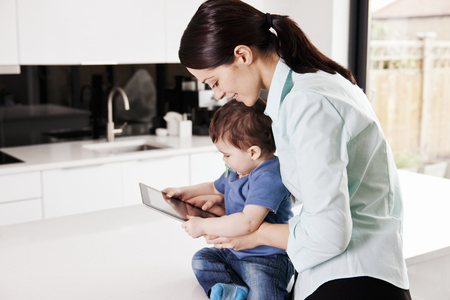 i pad: A mother with her baby son, looking at a digital tablet