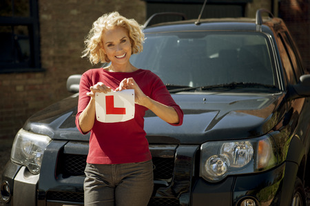 tearing: A mature woman tearing up a learner driver plate LANG_EVOIMAGES