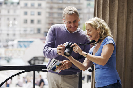 A middle-aged couple standing by Trafalgar Square, looking at photographs on their camera Imagens