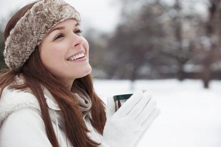Een jonge vrouw met een bont hoofdband met een hete drank Stockfoto