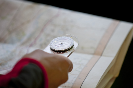 holding close: A man holding a map and compass, close up
