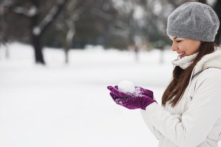 boule de neige: Une jeune femme tenant une boule de neige, sourire
