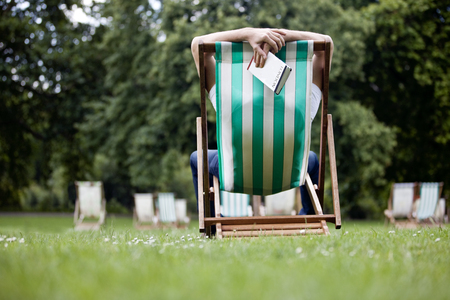 deckchair: A young man relaxing on a deckchair in St James Park, holding a guidebook