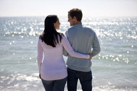 A pregnant woman and her partner standing on the beach, rear view