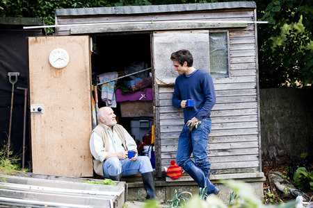 self sufficient: A father and his son having a break on an allotment, drinking tea LANG_EVOIMAGES