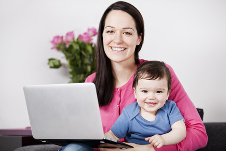 looking at baby: A mother using a laptop whilst holding her baby son on her lap