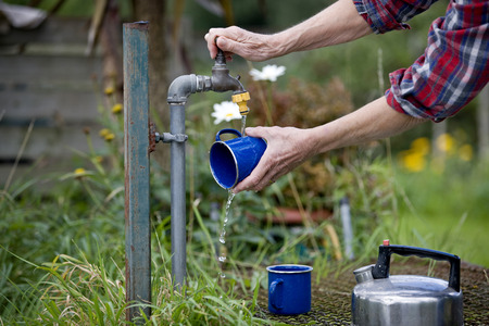 self sufficient: A senior woman washing cups on an allotment LANG_EVOIMAGES