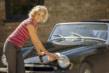 A mature woman washing a classic sports car Stock Photo