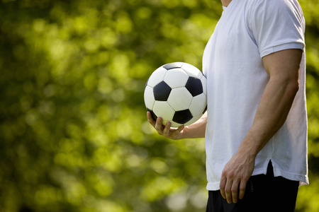 above 30: A young man holding a football, outdoors LANG_EVOIMAGES