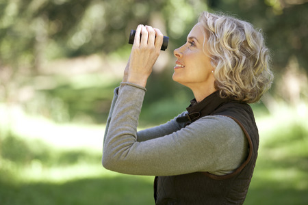 A mature woman outdoors, looking through a pair of binoculars
