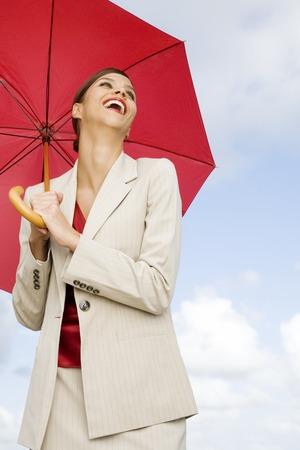A businesswoman standing underneath an umbrella