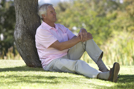 A senior man sitting under a tree