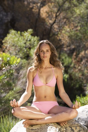 Young woman in a bikini practicing yoga LANG_EVOIMAGES