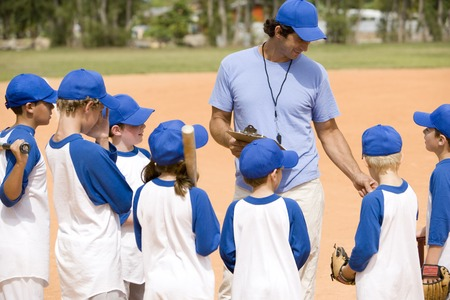 Little league baseball team and coach on pitch Imagens