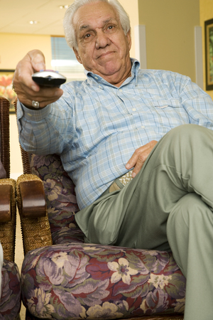 An elderly man using a TV remote control LANG_EVOIMAGES