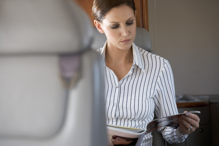 lear: A passenger reading a magazine on a flight
