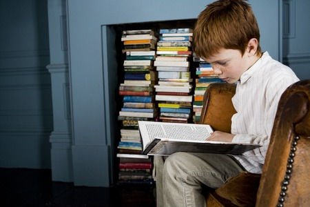 boy reading book sitting in armchair Stock Photo