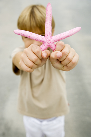beachcombing: A young boy holding a starfish LANG_EVOIMAGES
