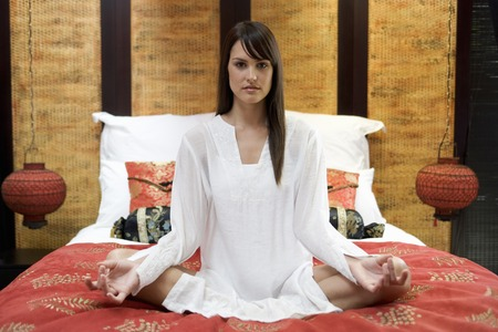 chillout: A woman sitting on a bed meditating