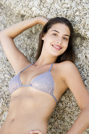 half length posed: A young woman lying on back on the sand LANG_EVOIMAGES