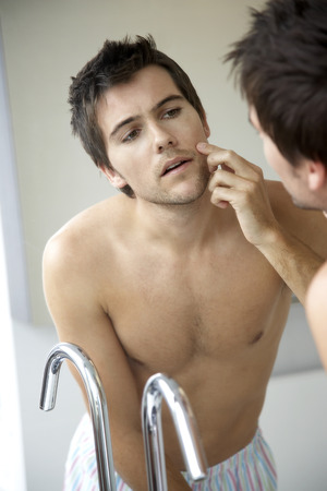 Young man looking at his reflection in a mirror