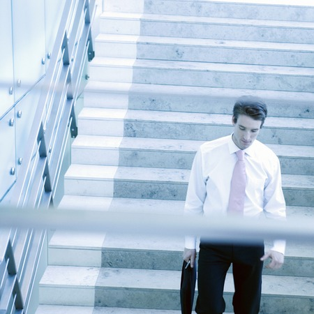 down stairs: A businessman walking down stairs