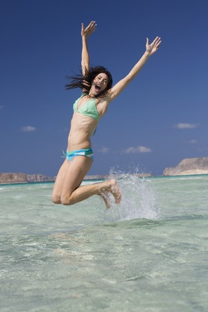 A woman jumping in the sea Stock Photo