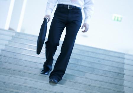 down the stairs: Un hombre de negocios caminando por las escaleras
