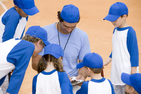 Little league baseball team and coach on pitch Stock Photo