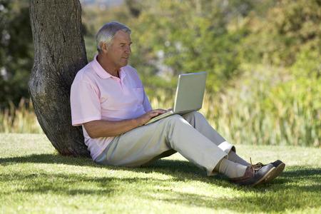 A senior man sitting under a tree using a laptop