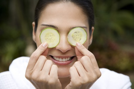 white robe: Smiling woman in a white robe with cucumbers over her eyes LANG_EVOIMAGES