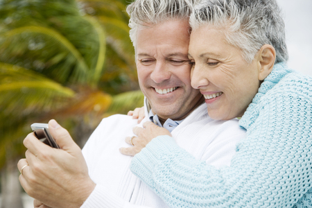 couple laughing: A senior couple reading a text message