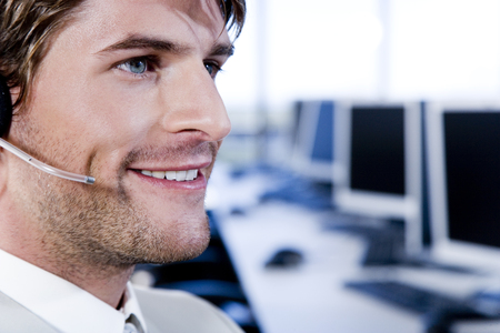 Smiling businessman in a call centre