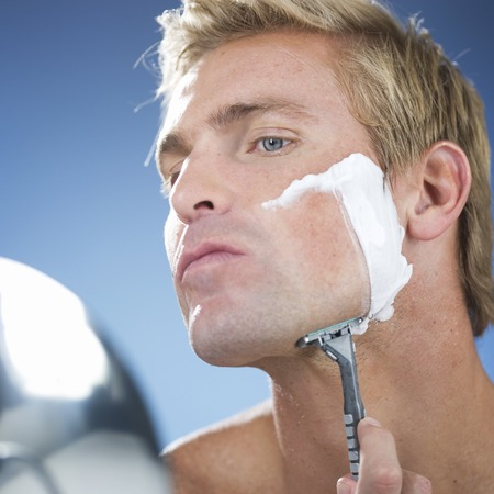 A young man shaving Stock Photo