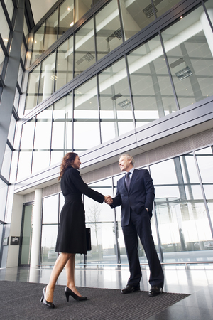 view of an atrium in a building: A businessman greeting a female client LANG_EVOIMAGES