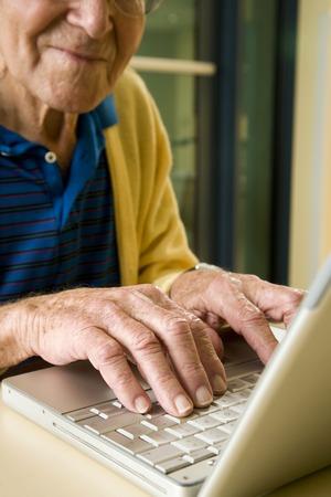 An elderly man using a laptop LANG_EVOIMAGES