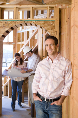 Portrait of man smiling by architect showing blueprint to woman in partially built house Stock Photo