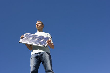 Man with solar panel, smiling, low angle view Stock Photo