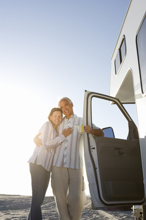Mature couple arm in arm by motor home on beach, smiling, low angle view (sun flare) Stock Photo