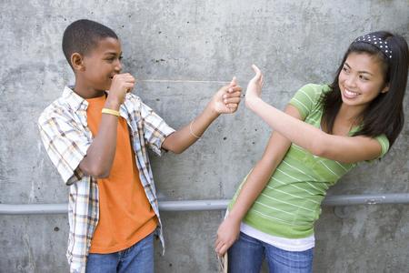 Teenage boy (13-15) preparing to flick rubber band at teenage girl (13-15), smiling