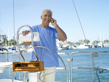 Man using mobile phone on boat, smiling, portrait