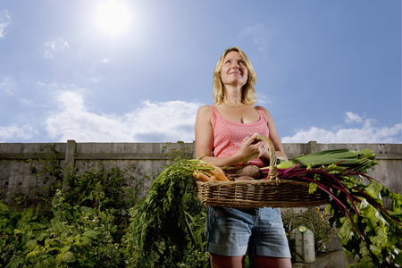 Woman in organic garden holding basket of vegetables