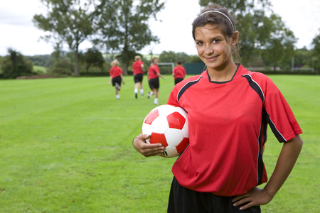 Portrait of teenage girl in uniform holding soccer ball Stock Photo